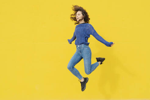 Young woman jumping in the air in front of yellow background - JCZF00032