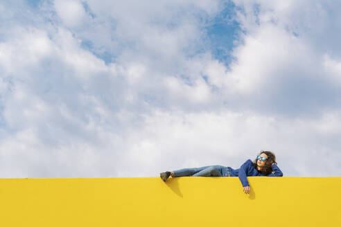 Young woman relaxing on yellow wall against cloudy sky - JCZF00035
