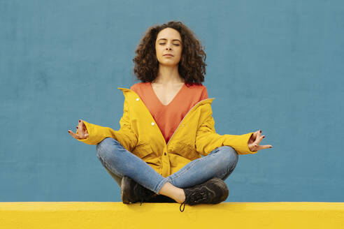 Portrait of young woman sitting on yellow wall in lotus position - JCZF00038