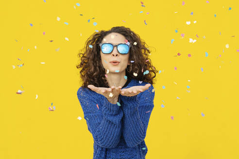 Portrait of young woman with mirrored sunglasses blowing confetti in the air in front of yellow background - JCZF00041