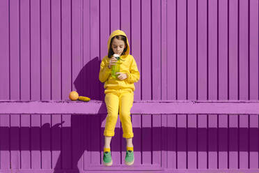 Little girl dressed in yellow sitting on bar in front of purple background drinking - ERRF03172