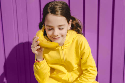Portrait of smiling girl dressed in yellow holding banana in front of purple background - ERRF03175