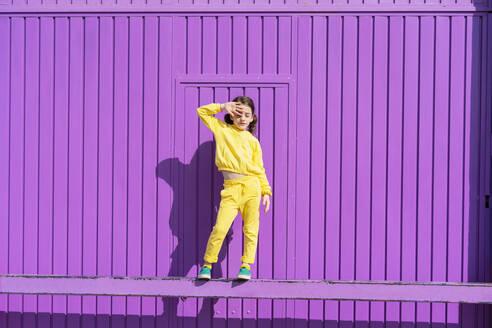 Little girl dressed in yellow standing on bar in front of purple garage door - ERRF03181