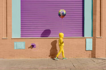 Little girl dressed in yellow walking on pavement with balloon - ERRF03184