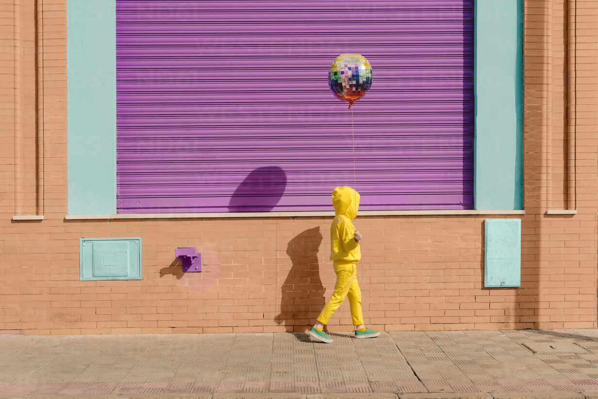 Little girl dressed in yellow walking on pavement with balloon - ERRF03184 - Eloisa Ramos/Westend61