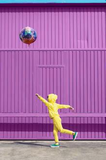 Children dressed in yellow standing in  front of purple garage door holding balloon - ERRF03187