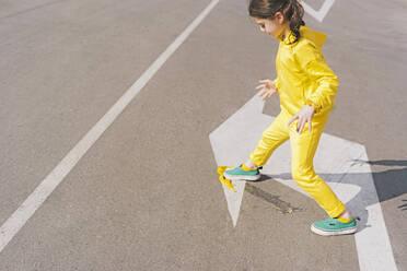 Girl stepping on banana peel on a street - ERRF03210