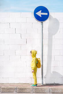 Girl standing on a traffic sign, direction left, in front of a white wall - ERRF03216