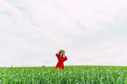 Woman wearing red dress and straw hat standing on a field - ERRF03219