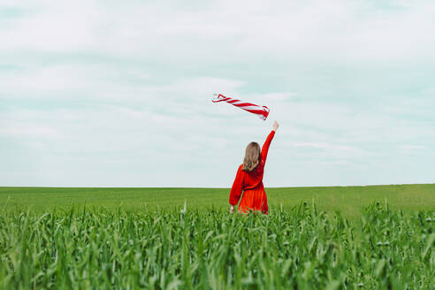 Back view of woman wearing red dress holding windsock on a field - ERRF03225