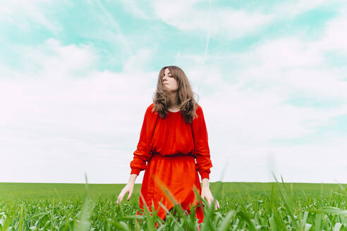 Woman wearing red dress relaxing in a field with eyes closed - ERRF03231