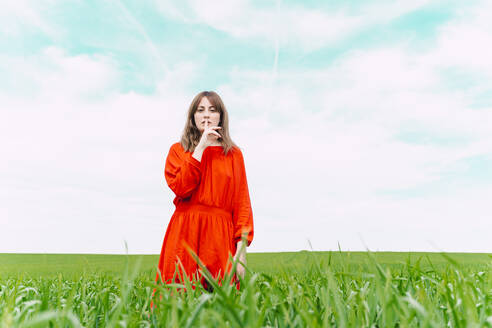 Portrait of woman wearing red dress standing in a field with finger on mouth - ERRF03237