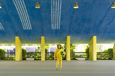 Little girl wearing yellow tracksuit holding soccer ball under her arm - ERRF03246