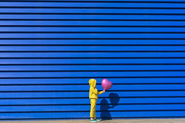 Little girl wearing yellow tracksuit  standing with pink balloon in front of blue background - ERRF03249