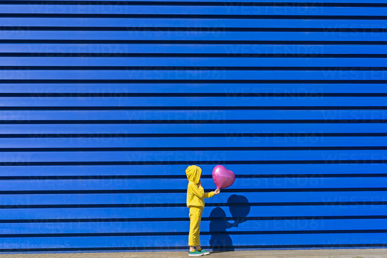 Little girl wearing yellow tracksuit  standing with pink balloon in front of blue background - ERRF03249 - Eloisa Ramos/Westend61