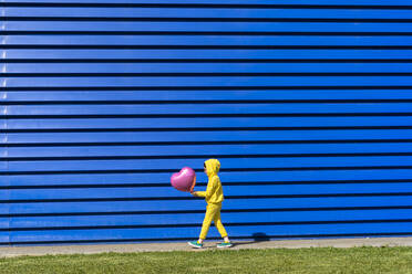 Little girl wearing yellow tracksuit walking with pink balloon in front of blue background - ERRF03252