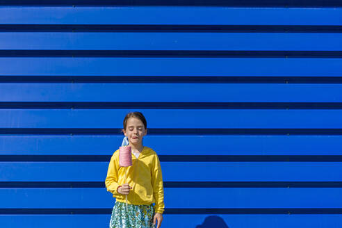 Little girl with fake ice cream standing in front of blue background licking lips - ERRF03255
