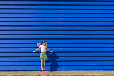 Little girl with colourful butterfly wings jumping in the air in front of blue background - ERRF03261