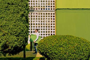 Mature man carrying green folder - ERRF03264