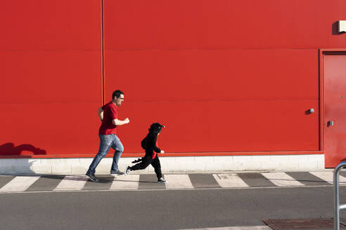 Man running together with his little girl wearing black fancy dress on zebra crossing - ERRF03270