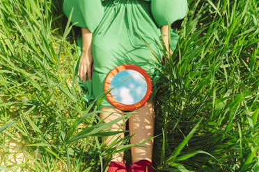 Crop view of young woman wearing green dress sitting on a field with mirror reflecting clouds - ERRF03279