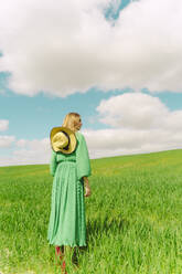 Back view of woman wearing green dress standing on a field - ERRF03282