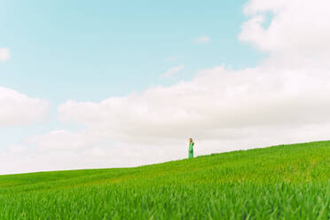 Woman wearing green dress standing on a field looking at distance - ERRF03285