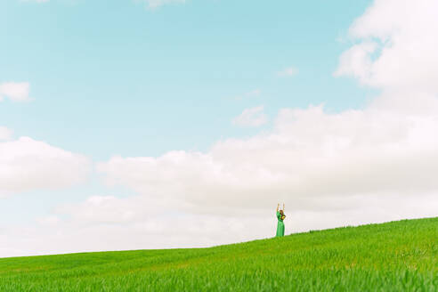 Back view of woman wearing green dress standing on a field with hands raised - ERRF03288