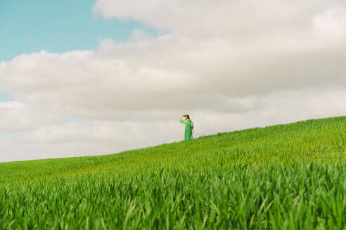Woman wearing green dress standing on a field looking at distance - ERRF03291