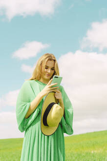 Young woman wearing green dress standing on a field using smartphone - ERRF03294