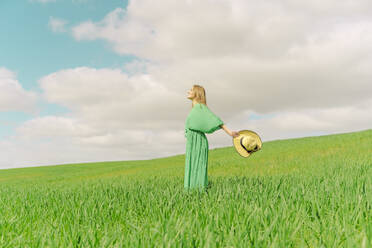 Blond young woman wearing green dress standing on a field - ERRF03297