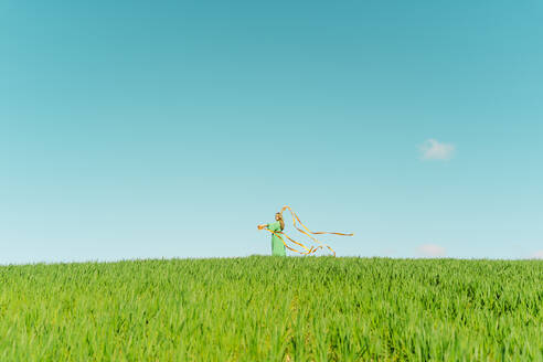 Blond young woman wearing green dress standing on a field with blowing ribbons - ERRF03300