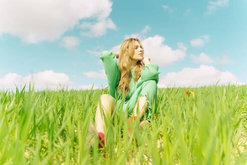 Blond young woman wearing green dress sitting on a field looking at distance - ERRF03303