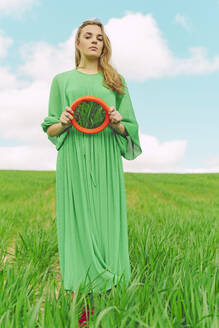 Portrait of young woman wearing green dress standing on a field holding reflecting mirror - ERRF03306