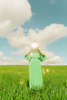 Young woman wearing green dress standing on a field holding hiding face behind reflecting mirror - ERRF03309