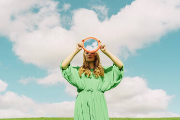 Young woman wearing green dress holding reflecting mirror - ERRF03312
