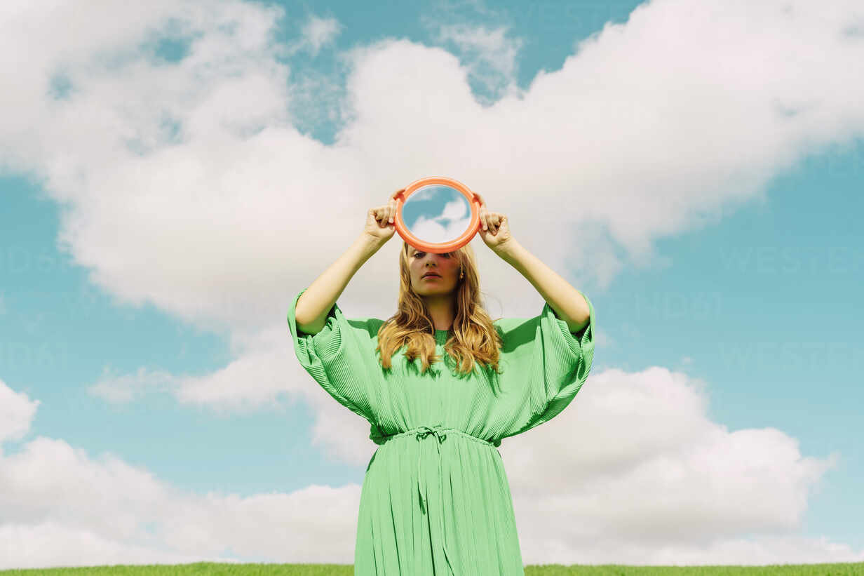 Young woman wearing green dress holding reflecting mirror - ERRF03312 - Eloisa Ramos/Westend61