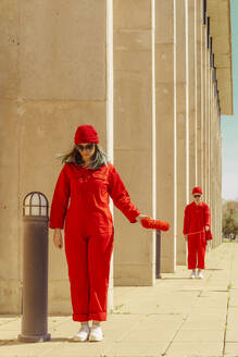 Young couple wearing red overalls and hats standing in a row connected with red string - ERRF03318
