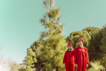 Young couple wearing red overalls and hats standing in nature looking at distance - ERRF03333