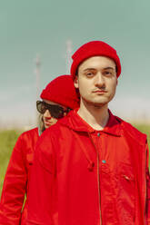 Portrait of young man and his girlfriend wearing red clothing outdoors - ERRF03339