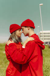 Young couple wearing red overalls and hats standing head to head looking at each other - ERRF03342