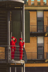 Young couple wearing red overalls and hats standing on platform looking at distance - ERRF03348