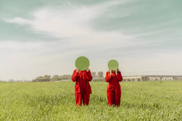 Young couple wearing red overalls  standing on a field hiding faces behind green circle - ERRF03351