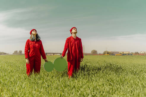Young couple wearing red overalls  standing on a field with two green circles looking up - ERRF03354