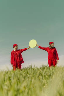 Young couple wearing red overalls  standing on a field holding green circle - ERRF03357