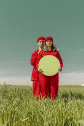 Young couple wearing red overalls and hats standing on a field with green circle - ERRF03360