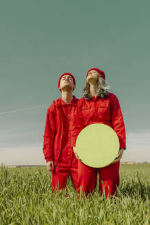 Young couple wearing red overalls  standing on a field with green circle - ERRF03363