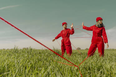 Young couple wearing red overalls and hats performing on a field with red string - ERRF03369