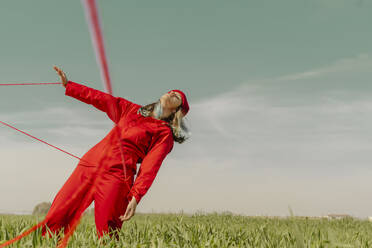 Young woman wearing red overall and hat performing on a field with red string - ERRF03372