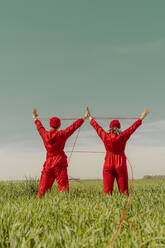 Back view of young couple wearing red overalls and hats performing on a field with red string - ERRF03375